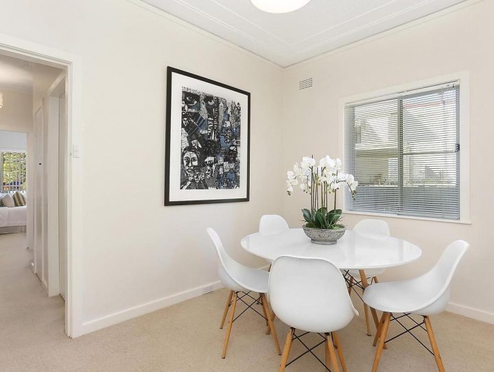 Modern dining table and chairs in white and timber legs