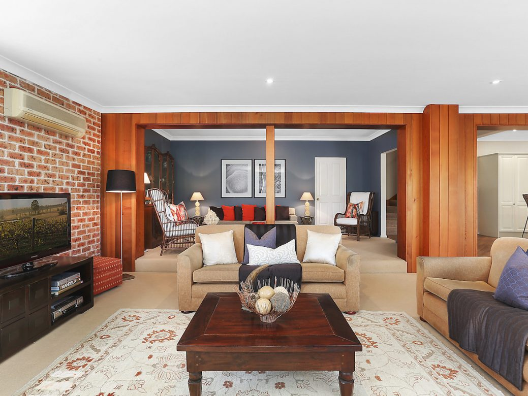 Family room and lounge area with brick wall and timber panelling